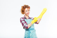 Happy housewife in blue apron wearing yellow gloves Stock Images