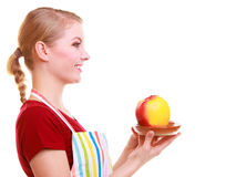 Happy housewife or chef in kitchen apron offering apple isolated Royalty Free Stock Photography
