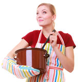 Happy housewife or chef in kitchen apron with pot of soup ladle Stock Photo