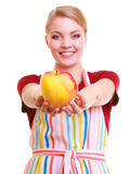 Happy housewife or chef in kitchen apron showing apple isolated Stock Photos