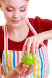 Happy housewife or chef in kitchen apron using apple timer. Happy housewife or chef in colorful kitchen using apple timer eggtimer isolated studio shot Stock Photo