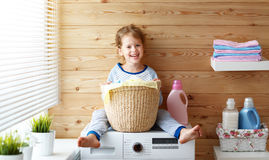 Happy  housewife child girl in laundry   with washing machine Stock Photos