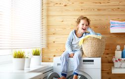 Happy  housewife child girl in laundry with washing machine Stock Photography