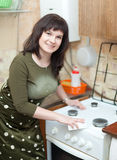 Happy housewife cleans the gas stove Royalty Free Stock Image