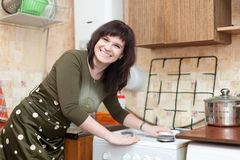 Happy housewife cleans the gas-stove Royalty Free Stock Photos
