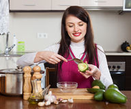 Happy housewife cooking with avocado Royalty Free Stock Images