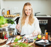 Happy housewife cooking saltwater fish in flour Stock Photography