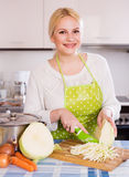 Happy housewife cooking shredded sauerkraut Stock Photos