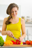 Happy housewife cutting bell pepper in kitchen Stock Images