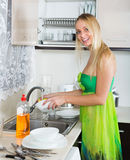 Happy  housewife in green washing dishes Royalty Free Stock Photography
