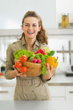 Happy housewife holding plate full of vegetables in kitchen Royalty Free Stock Images