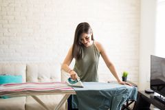Happy housewife ironing clothes. Cheerful young housewife wearing casuals ironing men`s shirt on ironing board Stock Images