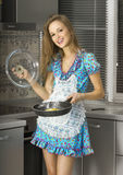 Happy housewife in the kitchen Royalty Free Stock Images