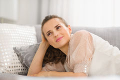 Happy housewife laying on sofa in living room Royalty Free Stock Photography