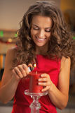 Happy housewife lighting red candle  in kitchen Royalty Free Stock Photography