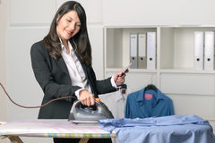Happy housewife listening to music while ironing Royalty Free Stock Image