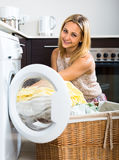 Happy housewife loading washing machine Royalty Free Stock Images