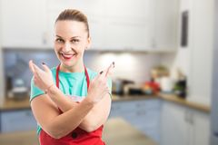 Happy housewife making good luck gesture with fingers crossed Stock Photo