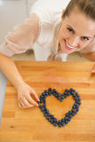Happy housewife making heart with blueberries