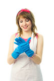 Happy housewife putting on blue rubber gloves Royalty Free Stock Images