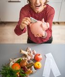 Happy housewife putting money into piggy bank after shopping. Happy young housewife putting money into piggy bank after shopping on local market Royalty Free Stock Photography