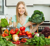 Happy housewife  with raw cabbage in home kitchen Royalty Free Stock Images