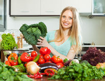 Happy housewife with raw cabbage and  vegetables Stock Photography