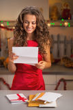 Happy housewife reading letter in christmas decorated kitchen Royalty Free Stock Images