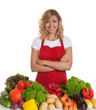 Happy housewife with red apron and fresh vegetables Royalty Free Stock Images