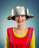 Happy housewife with sause pan on her head Stock Photo