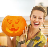 Happy housewife showing a big orange pumpkin Jack-O-Lantern Stock Photography
