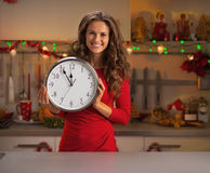Happy housewife showing clock in christmas decorated kitchen Royalty Free Stock Image