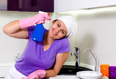 Happy housewife with a spray bottle of detergent Royalty Free Stock Images