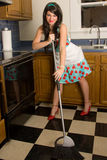 Happy Housewife Sweeping Kitchen. A fun, cute image with a retro feel of a beautiful smiling woman in pearls, heels, and a dress sweeping the kitchen floor Royalty Free Stock Photos