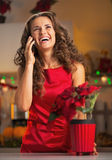 Happy housewife talking phone in christmas decorated kitchen Royalty Free Stock Images