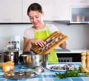 Happy housewife trying new recipe. Of sprattus in kitchen Stock Photo