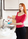 Happy housewife  washing plates with  detergent Royalty Free Stock Photos