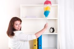 Happy Housewife wipes the dust off the shelves Stock Photo