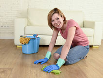 Happy housewife woman with beautiful smile cleaning house washing floor kneeling. Young happy and attractive housewife or woman with red hair and beautiful smile stock images
