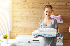 Happy housewife woman in laundry room with washing machine. A Happy housewife woman in laundry room with washing machine royalty free stock photography