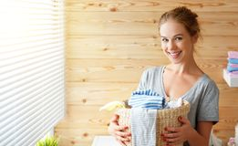 Happy housewife woman in laundry room with washing machine Stock Photography