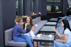 Happy housewives meeting at cafe and drinking coffee. Concept of free time and gossips Stock Images