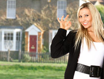 Happy housing agent. A very happy estate agent promoting a house showing a gesture for perfection Royalty Free Stock Photos