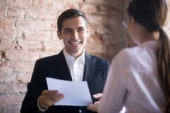 Happy hr manager with resume looking at female job seeker. Happy hr manager with resume in hands looking at female job seeker. Smiling recruiter and candidate stock photography