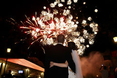 Happy hugging bride and groom watching beautiful colorful firewo Stock Photography