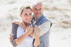 Happy hugging couple on the beach looking at camera Stock Photo