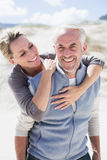 Happy hugging couple on the beach looking at camera Royalty Free Stock Photos