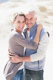 Happy hugging couple on the beach looking at camera Royalty Free Stock Photography