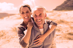 Happy hugging couple on the beach looking at camera. On a bright but cool day Royalty Free Stock Images