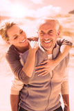 Happy hugging couple on the beach looking at camera. On a bright but cool day Stock Images